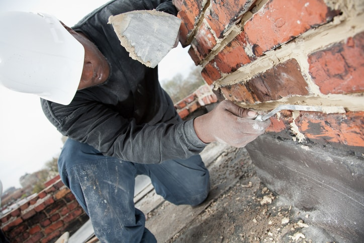 Masons smooths mortar joint in chimney.